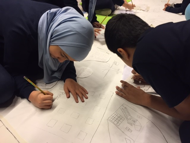 2 students drawing on pieces of paper