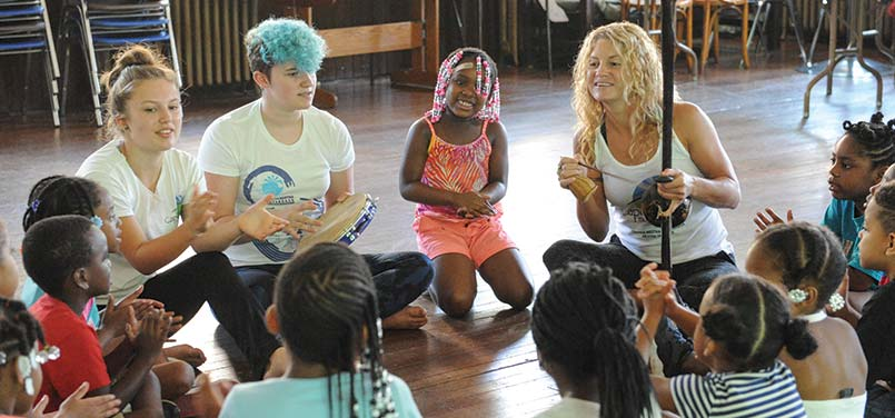Children in a circle learning an african musical insrtuments