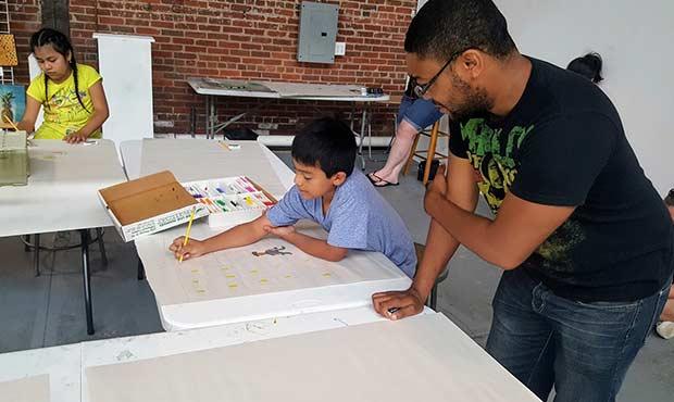 Photo of Rashad Malik Davis working with a Student