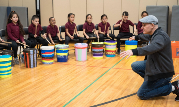 Caption: Teaching artist Josh Robinson leads a warm-up for the students of Washington Avenue Elementary School. Photography by Driven by Design Creative Agency, LLC.